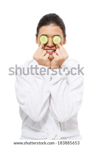 beautiful young woman in bathrobe with cucumber on eyes. isolated on white.  - stock photo