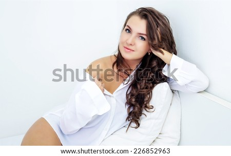 beautiful young woman in bed at home - stock photo