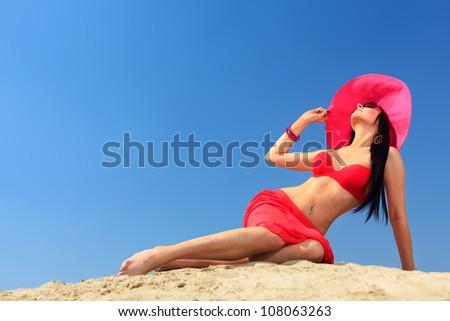 Beautiful young woman in bikini on a sunny beach. - stock photo