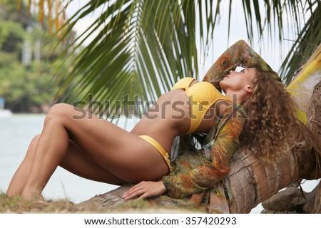 Beautiful young woman in bikini on palm in tropical sea beach - stock photo
