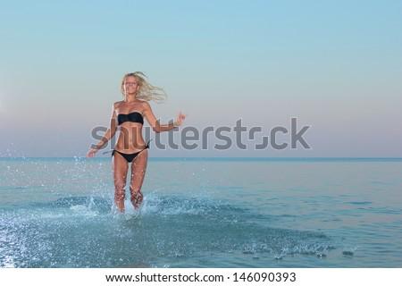 Beautiful young woman in bikini on the beach - stock photo
