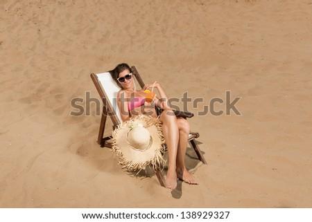 Beautiful young woman in bikini on the beach enjoying a fresh cocktail - stock photo