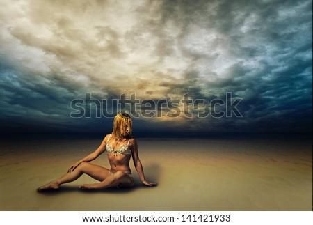 Beautiful young woman in bikini on the beach with dramatic sky - stock photo