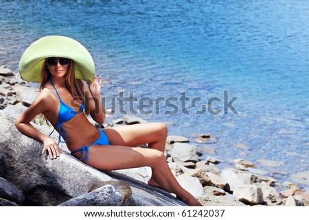 Beautiful young woman in bikini posing on a sea beach. - stock photo