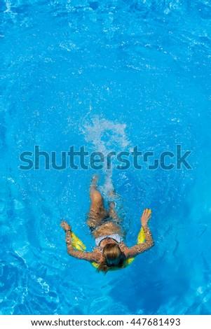 Beautiful young woman in bikini Relaxing in a swimming pool - stock photo