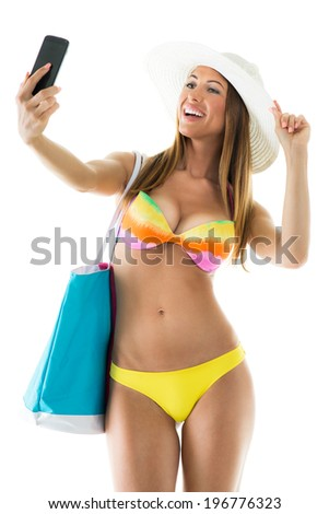Beautiful young woman in bikini with Sun Hat and holding beach bag. She is taking a selfie. Isolated on white background - stock photo