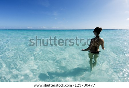 Beautiful young woman in black bikini standing in the shallow ocean - stock photo