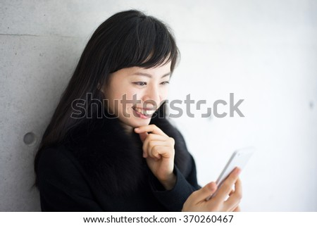 beautiful young woman in black coat holding smart phone - stock photo