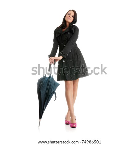 Beautiful young woman in black coat pink high heels with blue umbrella isolated on white background - stock photo