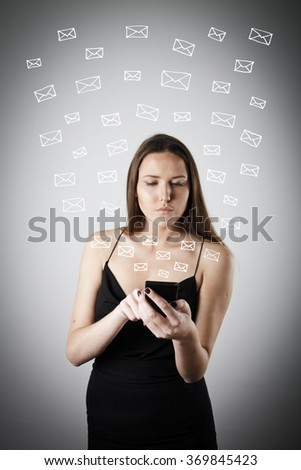 Beautiful young woman in black is using a mobile phone. E-mail concept.  - stock photo