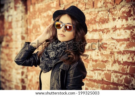 Beautiful young woman in black leather jacket posing over brick wall. - stock photo