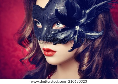 Beautiful young woman in black mysterious  Venetian mask. Fashion photo - stock photo