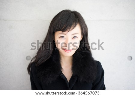 beautiful young woman in black overcoat - stock photo
