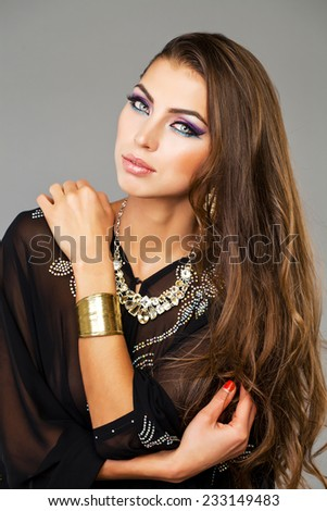 Beautiful young woman in black tunic Arabic, on gray background  - stock photo