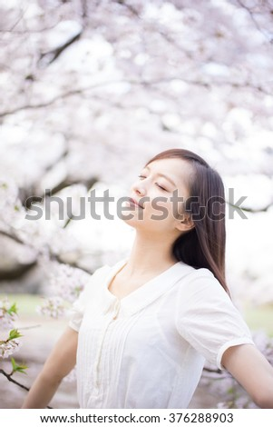 beautiful young woman in blooming cherry blossoms garden - stock photo