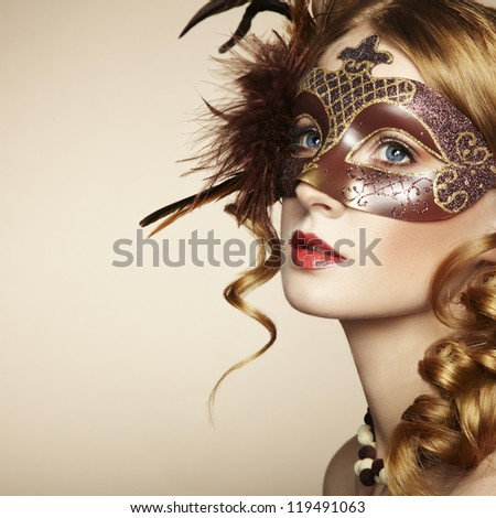 Beautiful young woman in brown mysterious venetian mask. Fashion photo - stock photo