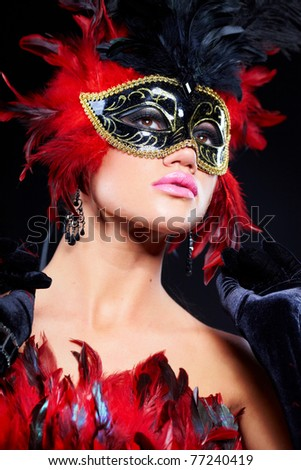 Beautiful young woman in carnival mask and feather boa. - stock photo