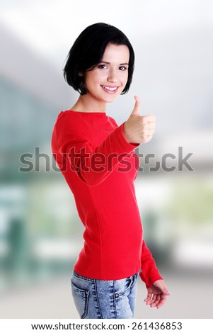 Beautiful young woman in casual clothes gesturing thumbs up. - stock photo