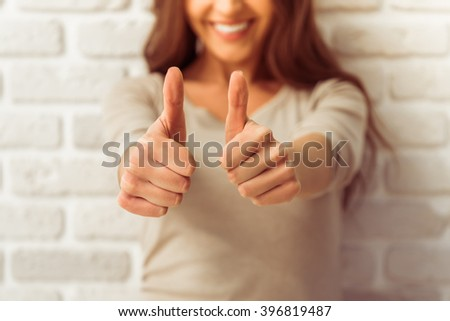 Beautiful young woman in casual clothes is showing Ok sing, looking at camera and smiling, against white brick wall, close up - stock photo