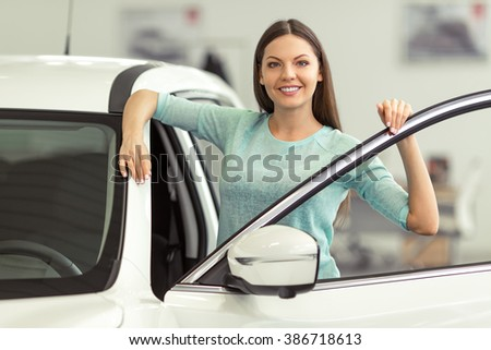 Beautiful young woman in casual clothes is smiling and looking at camera while leaning on a new car in a motor show - stock photo