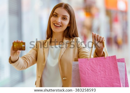 Beautiful young woman in casual clothes smiling, holding shopping bags and a credit card while standing in mall - stock photo