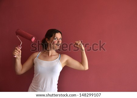Beautiful young woman in causal clothes showing muscles and feeling empowered  and happy by the job she had done painting a wall with red paint and a roller - stock photo