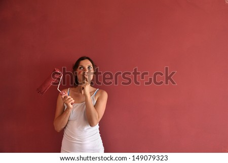 Beautiful young woman in causal clothes thinking about the result of the work she has done painting a wall with red paint and a roller - stock photo