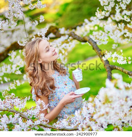Beautiful young woman in cherry blossom garden with cup of tea or coffee on a spring day - stock photo