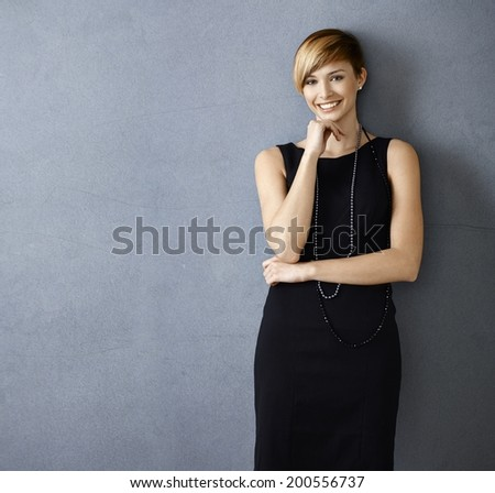 Beautiful young woman in cocktail dress on gray background - stock photo