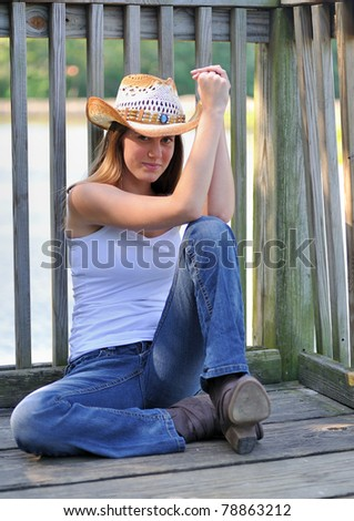 Beautiful young woman in country or western attire sitting on a dock in shade - cowboy hat, boots, and jeans - stock photo