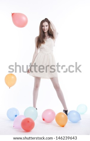 Beautiful young woman in dress with balloons on floor against white background - stock photo