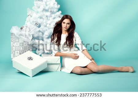 beautiful young woman in elegant dress standing next to white christmas tree and presents.  - stock photo