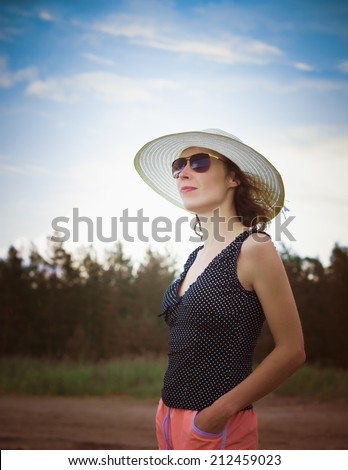 Beautiful young woman in elegant hat and sunglasses posing over sky. - stock photo