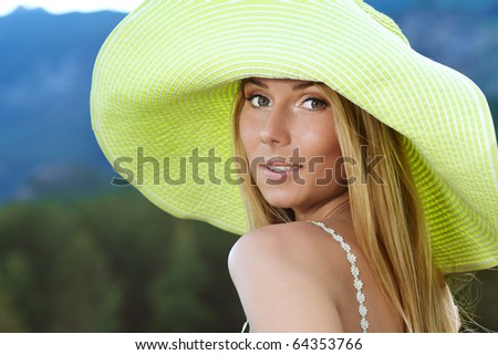 Beautiful young woman in elegant hat posing over landscape. - stock photo