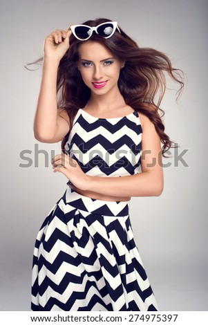 Beautiful young woman in elegant summer clothes and sunglasses posing in studio, smiling at the camera - stock photo