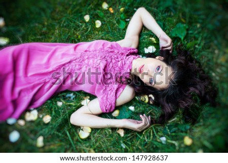 beautiful young woman in elegant summer dress lie in grass - stock photo