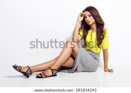 Beautiful young woman in fashionable clothes, sunglasses, grey skirt, yellow top, sandals with long wavy hair looking at camera. Fashion photo - stock photo