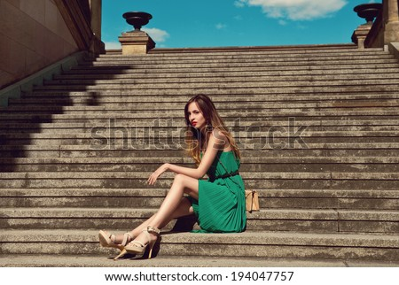 beautiful young woman in fashionable green dress standing on stairs - stock photo