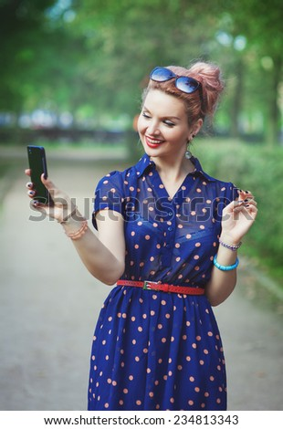 Beautiful young woman in fifties style with braces taking picture of herself  - stock photo