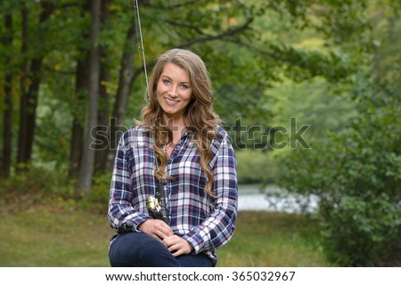 Beautiful young woman in flannel shirt with fishing pole - country girl gone fishing' - stock photo