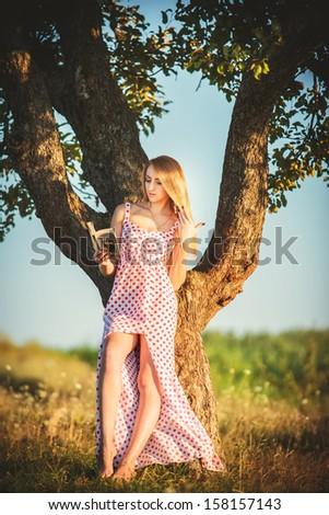beautiful young woman in garden reading. - stock photo