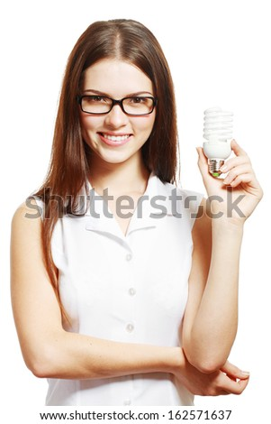 beautiful young woman in glasses holding energy saving lamp bulb - stock photo