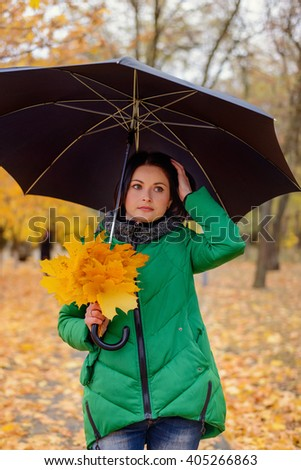 Beautiful young woman in green coat holding large yellowed maple tree leaves while looking sideways with calm expression - stock photo