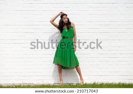 Beautiful young woman in green dress, against white wall - stock photo