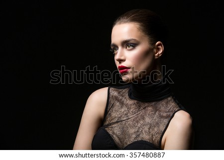 Beautiful young woman in lace top with red lips. Over black background. Copy space. - stock photo