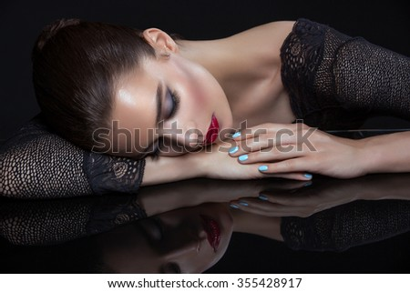 Beautiful young woman in lace top with red lips touching face. Over black background. Copy space. - stock photo