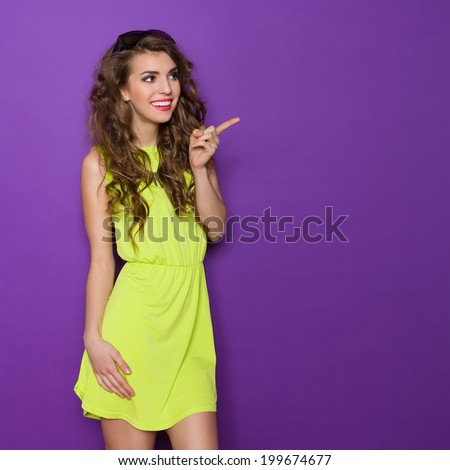 Beautiful young woman in lime dress is pointing and looking away. Three quarter length studio shot on violet background. - stock photo