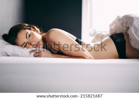 Beautiful young woman in lingerie lying in her bed looking away thinking. Thoughtful female model resting on bed. - stock photo