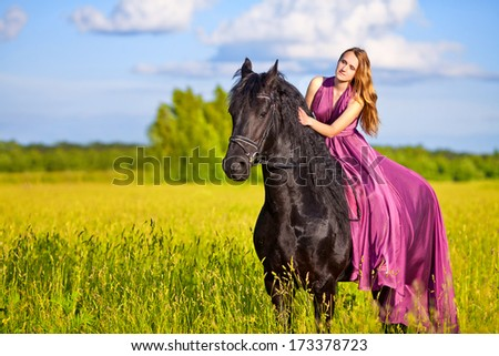 Beautiful young woman in long red dress on a horse outdoor - stock photo