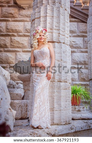 beautiful young woman in love in the park a wreath on his head, holding flowers in their hands summer - stock photo